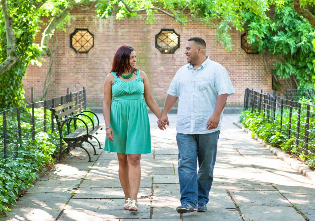 Couple holding hands and walking along Conservatory Garden pathway during a Central Park engagement shoot