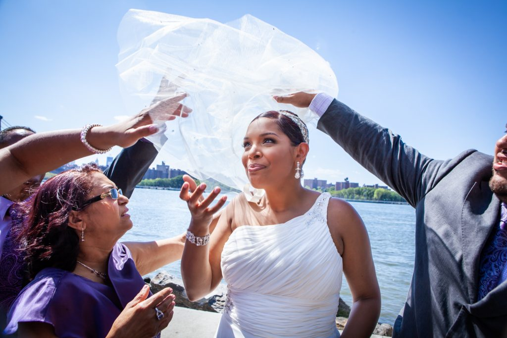 Bride by river with veil blowing in wind before her Attic Studios wedding