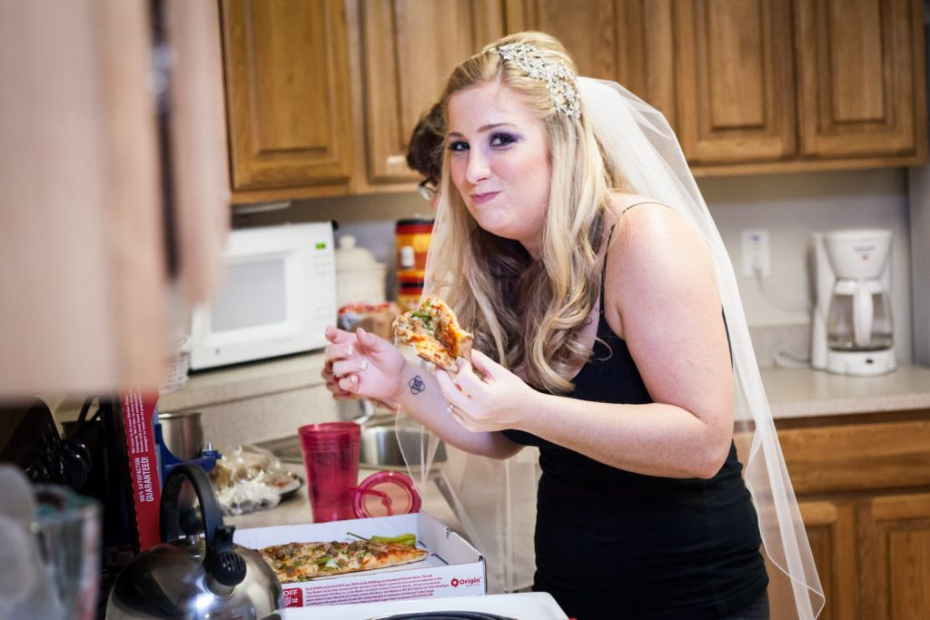Bride wearing veil and eating pizza before her Fort Hamilton Community Club wedding