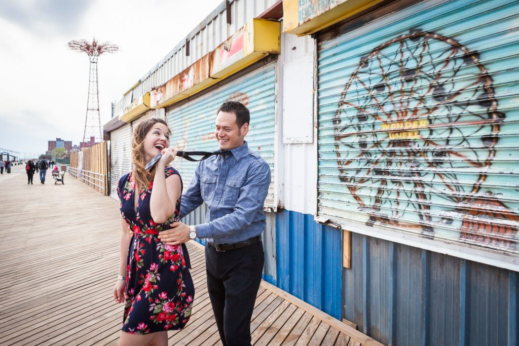 Woman pulling man by his tie on boardwalk or an article on Coney Island engagement photo tips