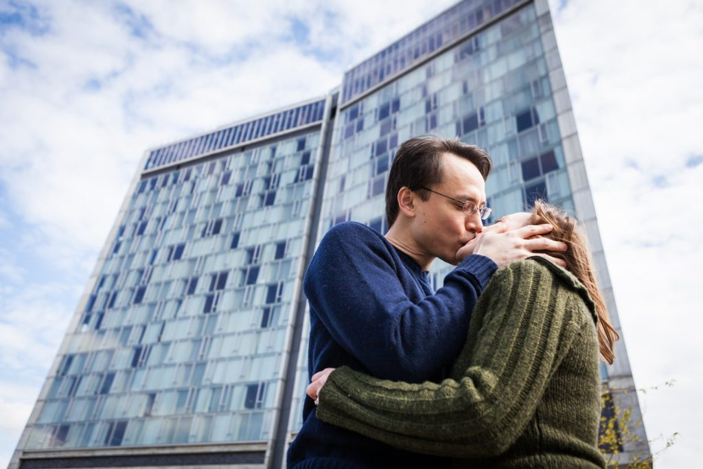 Couple kissing under Standard Hotel during a High Line engagement portrait session