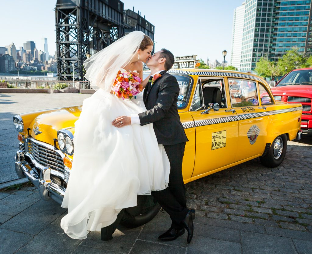 Groom kissing bride on top of old NYC taxicab before a Ravel Hotel Penthouse wedding