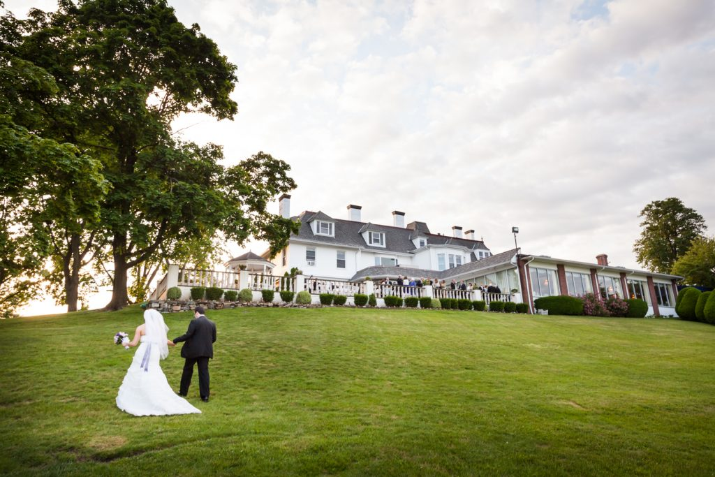 Bride and groom walking up front lawn at a Davenport Mansion wedding