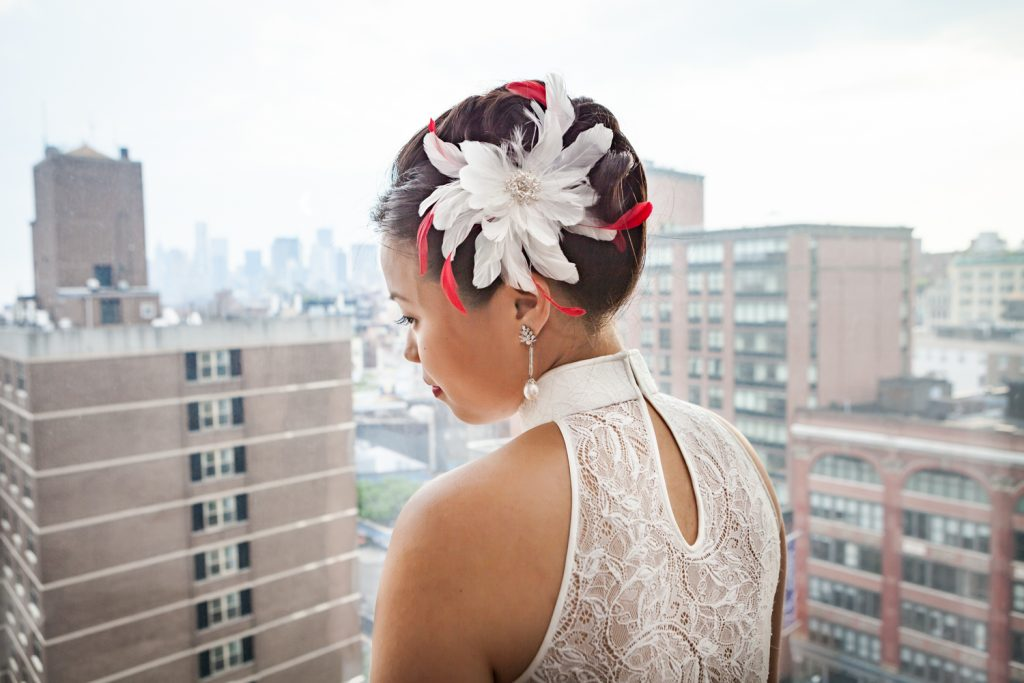 Bride with feathered barrette in hair in front of window for a Merchant's House Museum wedding