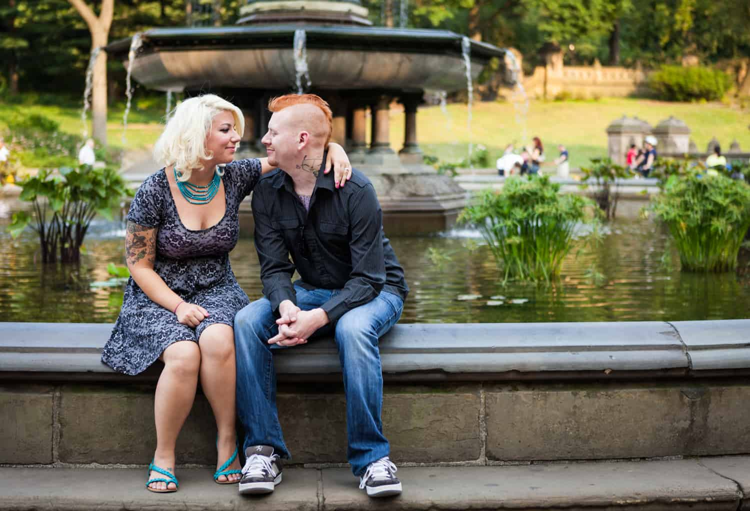 Central Park engagement photos of couple sitting on the side of Bethesda Fountain