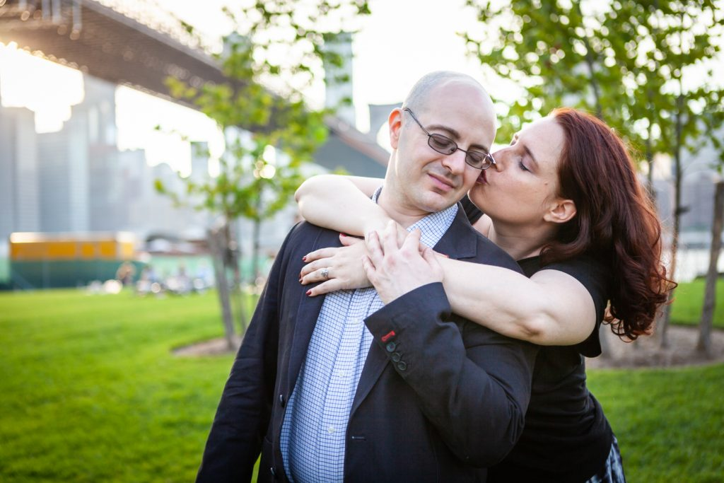 Woman kissing man on cheek during a Brooklyn Bridge Park engagement portrait session