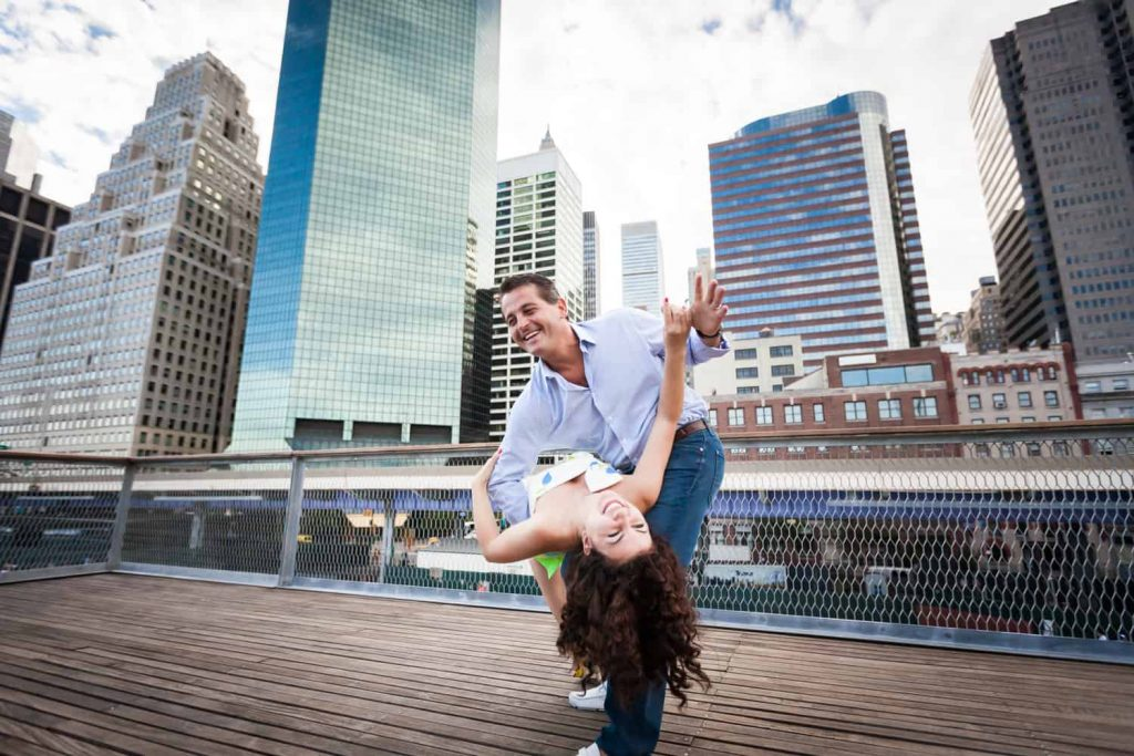 Financial District engagement photos of couple dancing in front of NYC skyscrapers