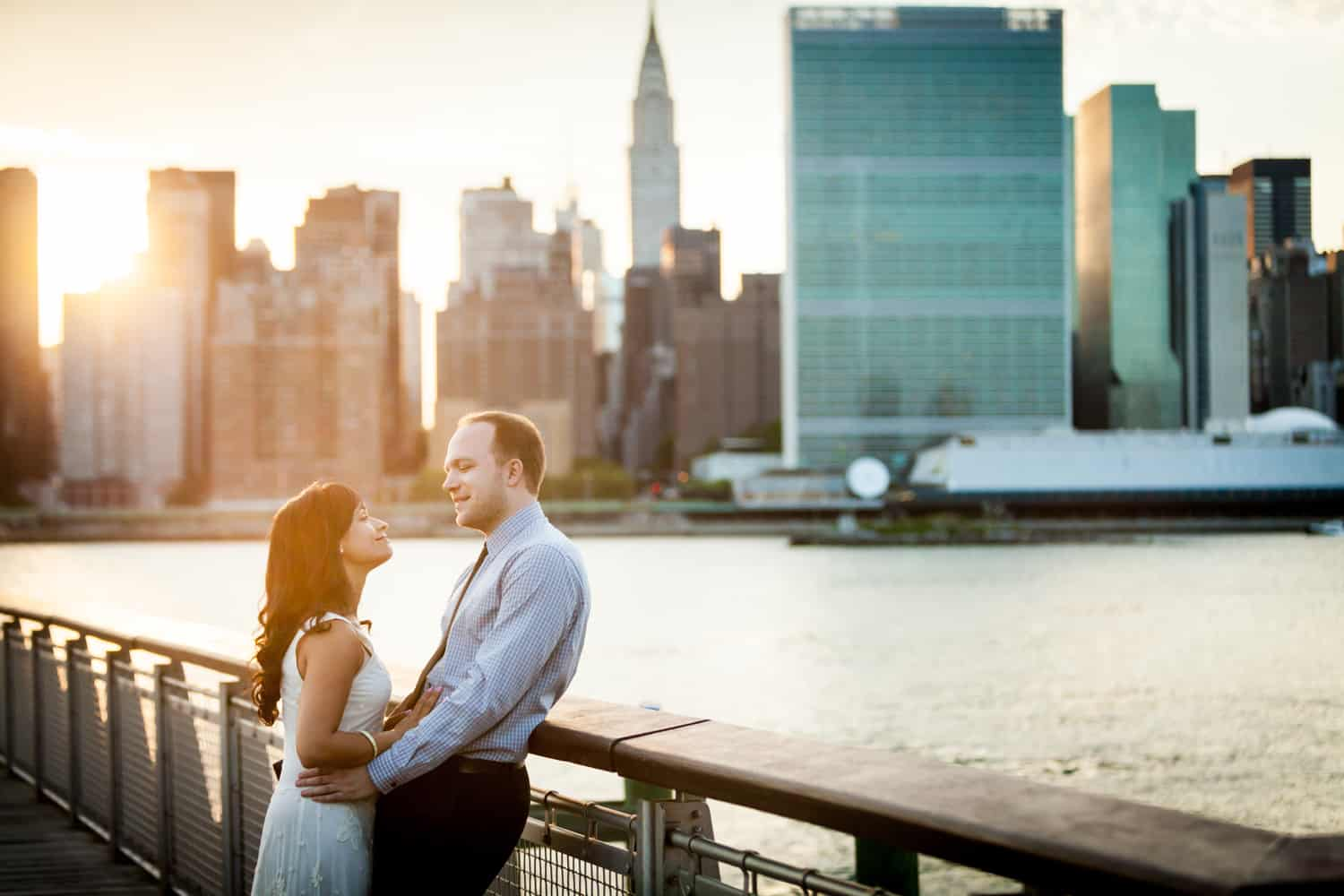 Couple leaning against railing at a Gantry Plaza State Park engagement shoot