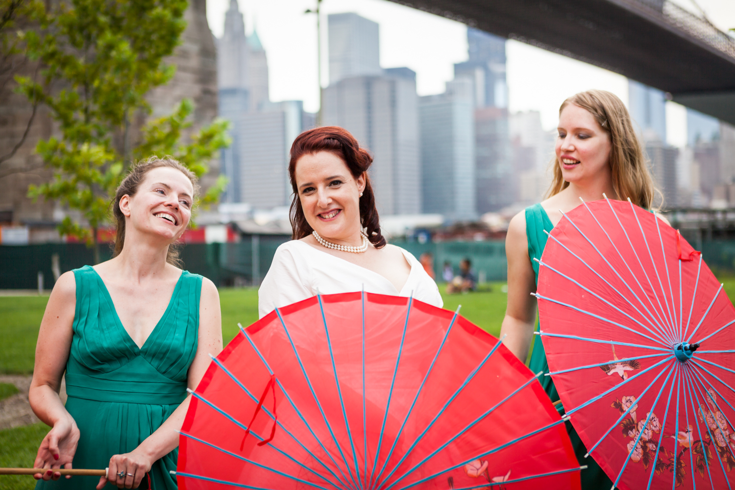 Bride and two bridesmaids with red umbrellas at a DUMBO wedding