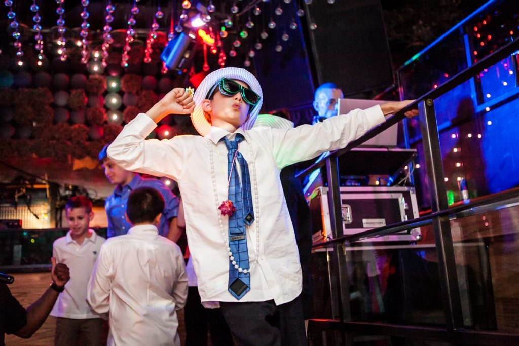 Young boy in sunglasses dancing at a Manhattan bar mitzvah by bar mitzvah photojournalist, Kelly Williams