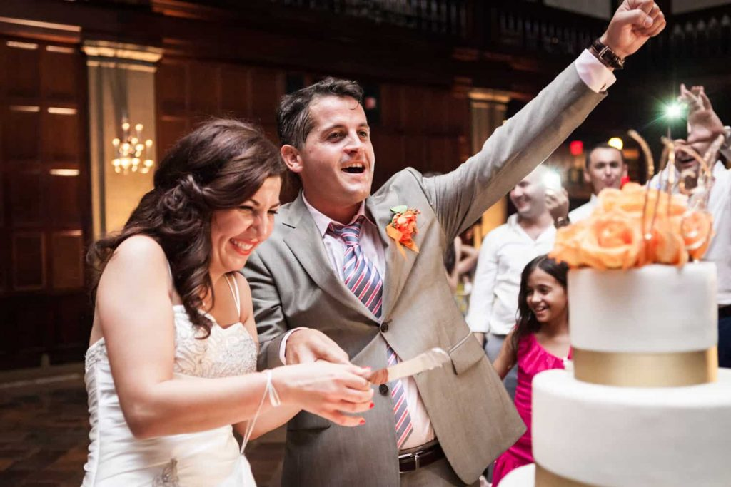 Groom cheers after cutting cake with bride at a Harvard Club wedding