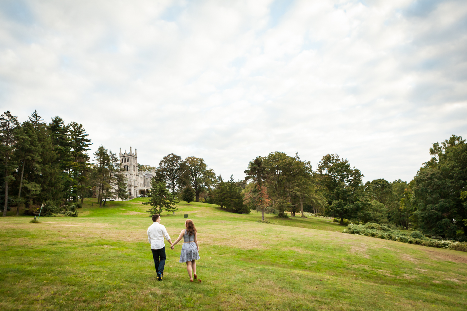 Couple holding hands and walking across field during a Lyndhurst Mansion engagement session