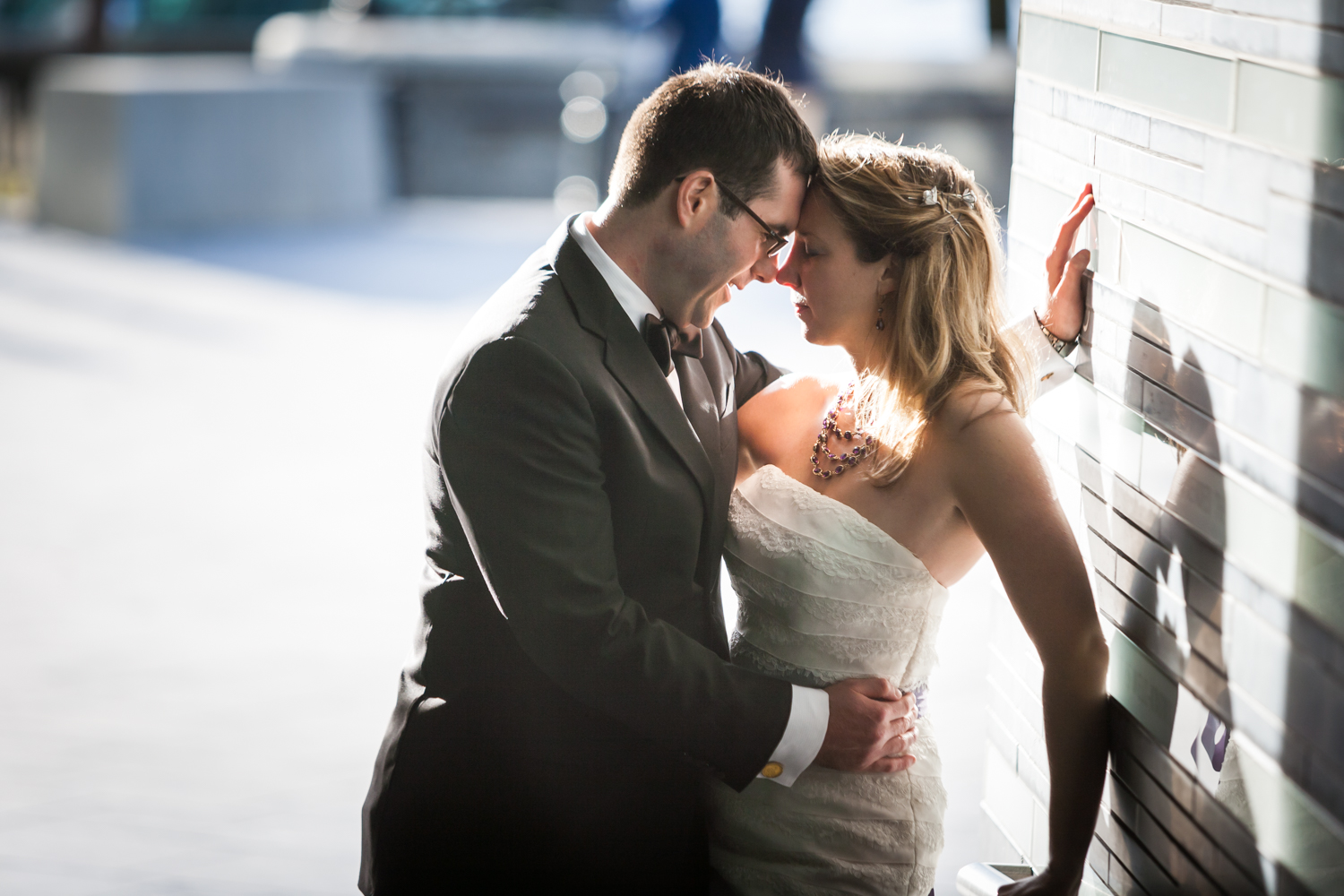 Groom and bride touching foreheads against wall at a trash the dress shoot