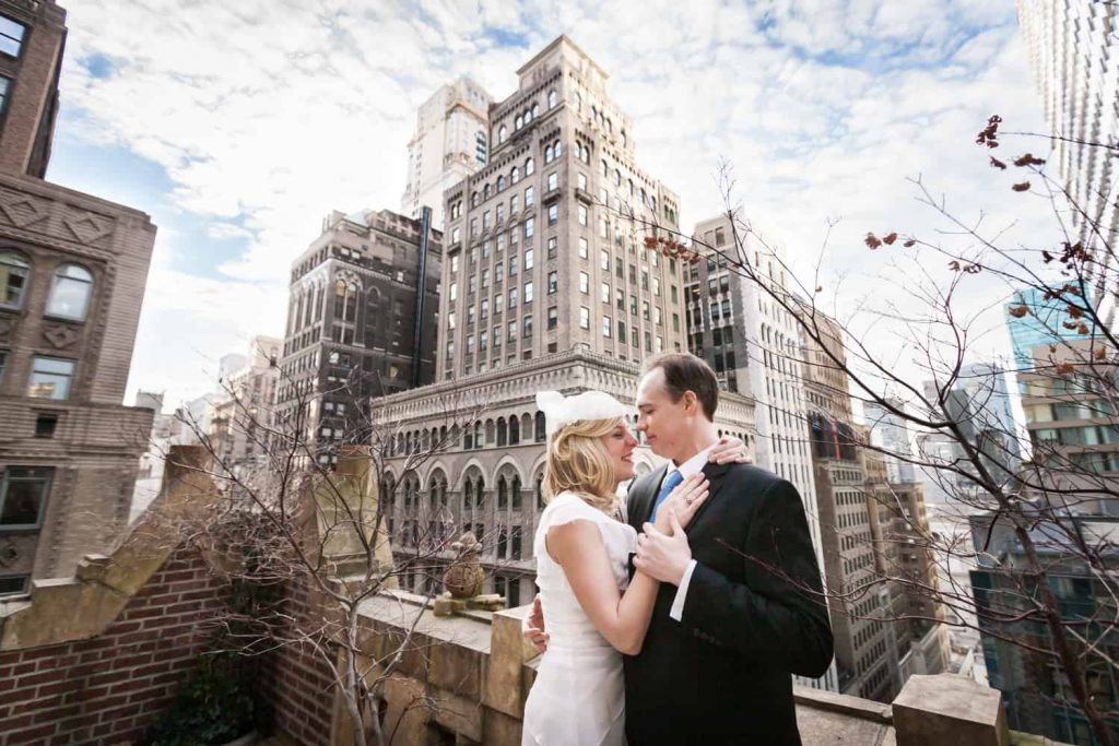 Couple hugging with NYC skyline in background before a Library Hotel wedding