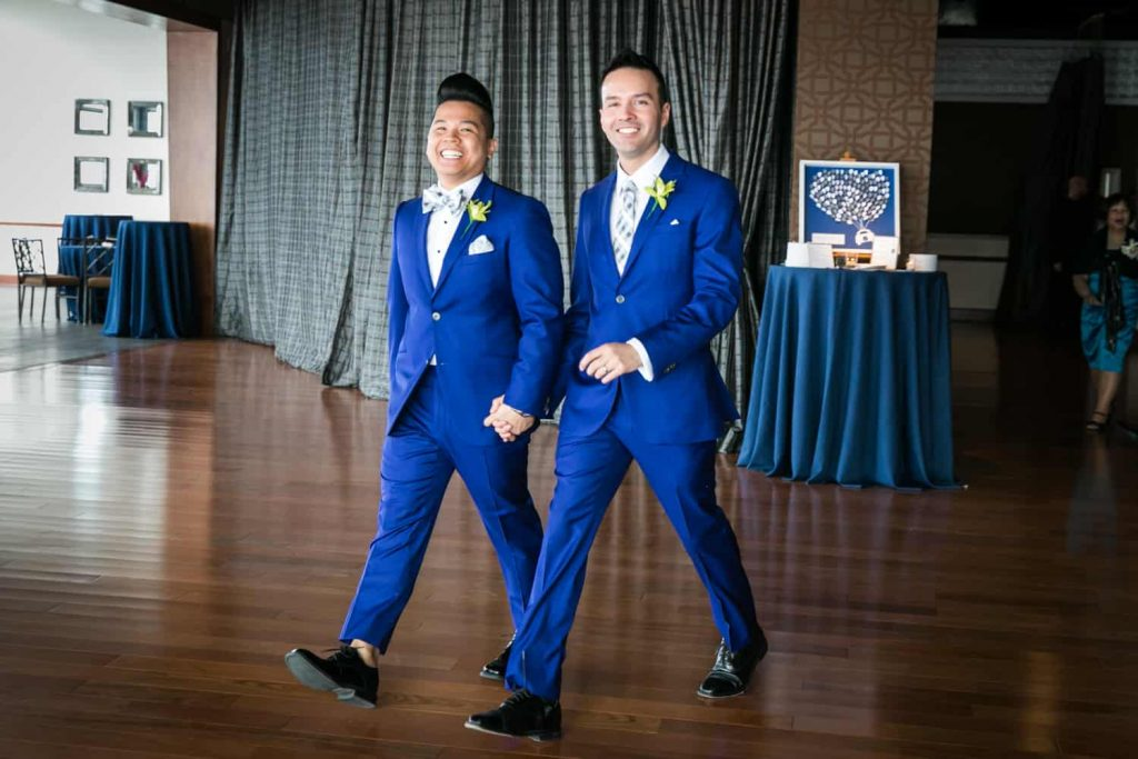 Two grooms in blue suits entering reception at a Lighthouse at Chelsea Piers wedding