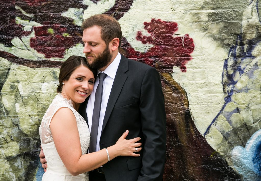 Portrait of bride and groom with colorful mural in background