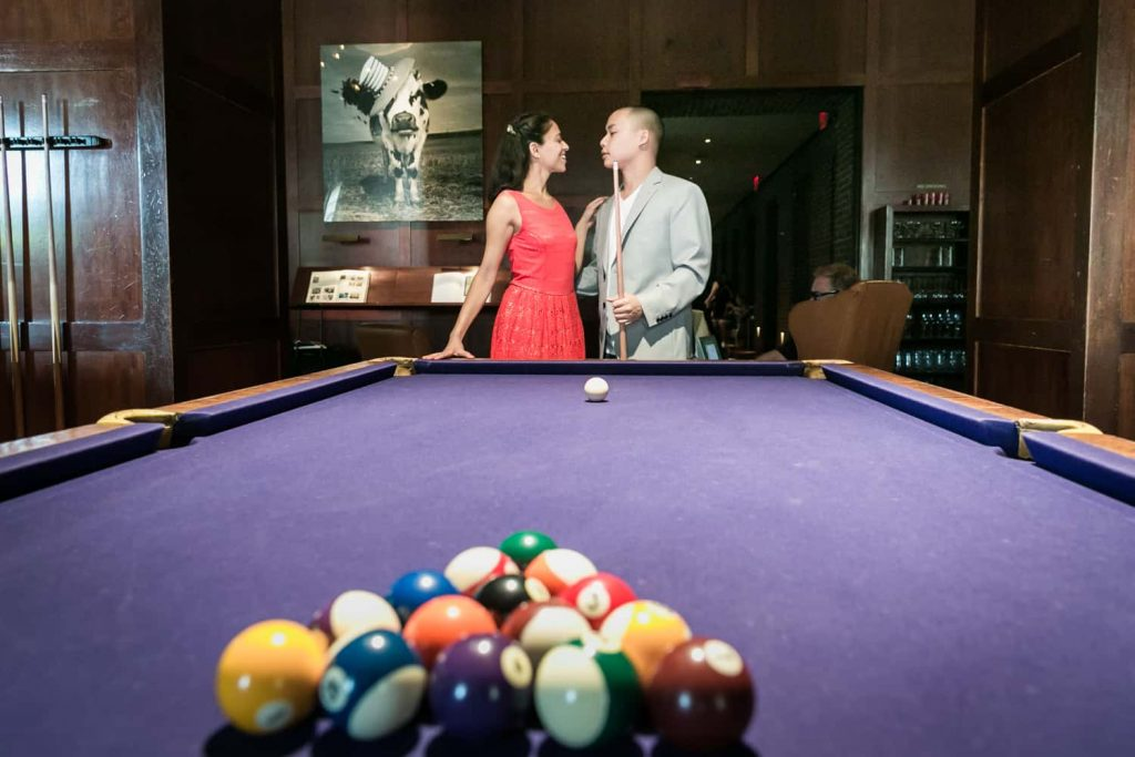 Couple at end of pool table during a Hudson Hotel engagement shoot