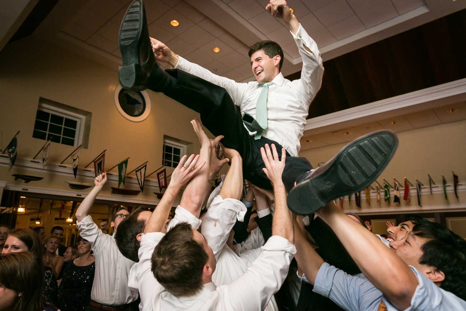 Groom thrown in the air by guests on the dance floor at an American Yacht Club wedding