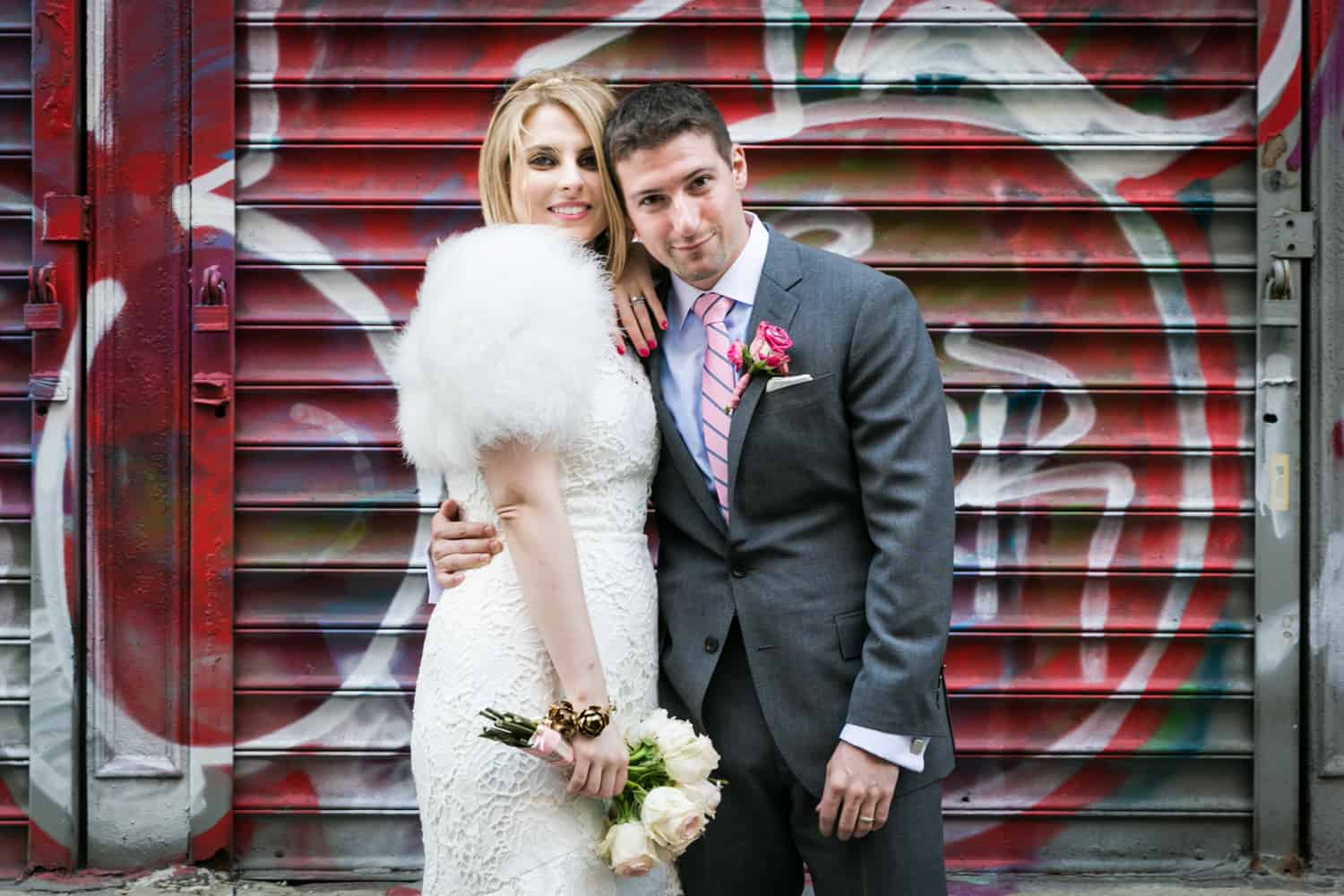 Bride and groom hugging in front of graffiti covered metal gate