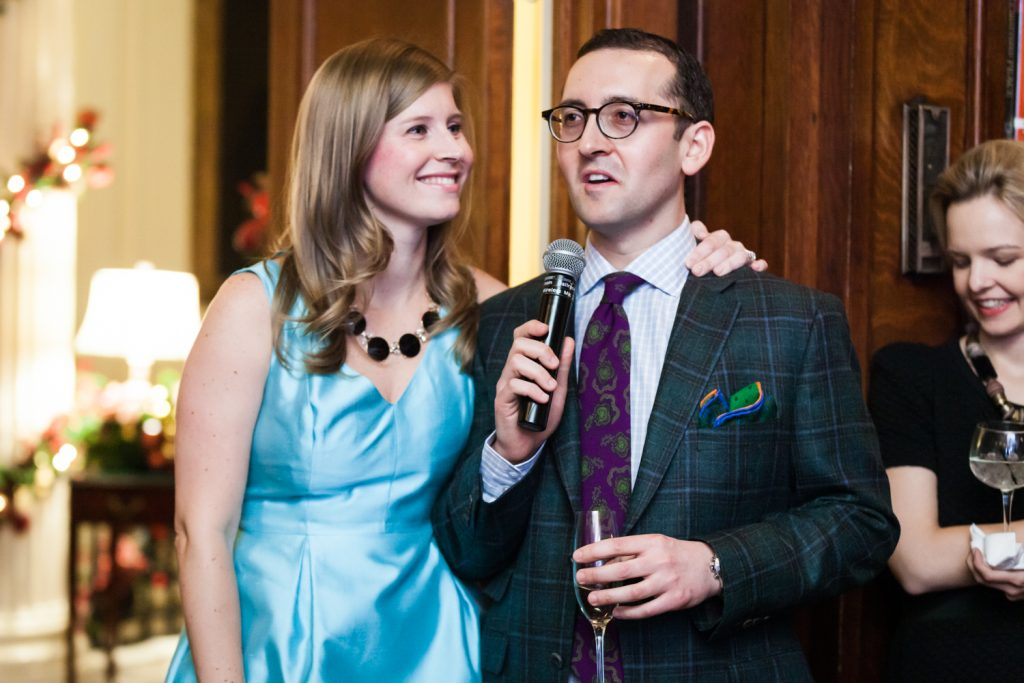 Man speaking into microphone and woman wearing blue dress at a Lotos Club engagement party