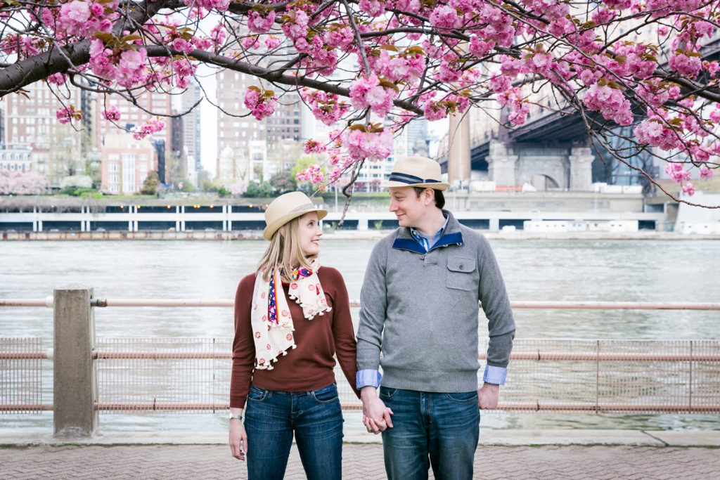 Couple holding hands with cherry blossom branches overhead during a Roosevelt Island engagement portrait session