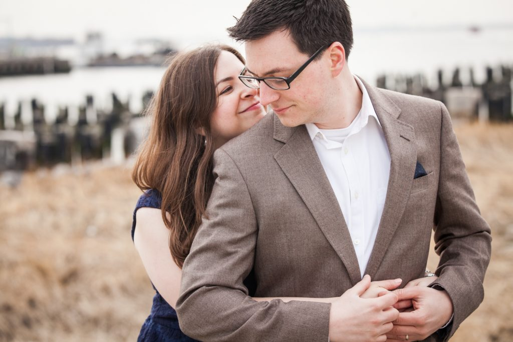 Brooklyn Promenade engagement photos of couple hugging with abandoned dock in background