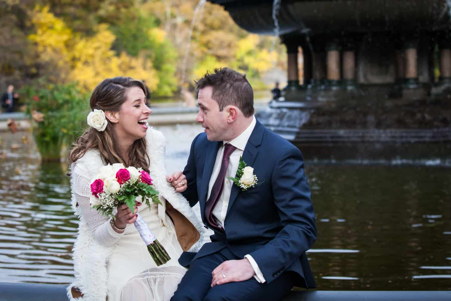 Bride and groom laughing at a Bethesda Fountain wedding in Central Park