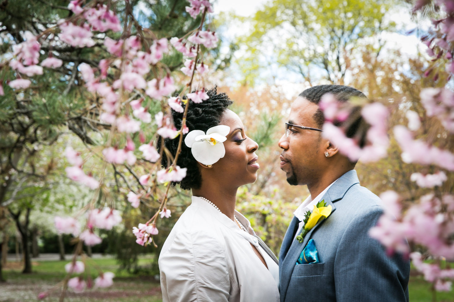 Portrait of bride and groom under cherry blossom trees at a Flushing Meadows Corona Park wedding