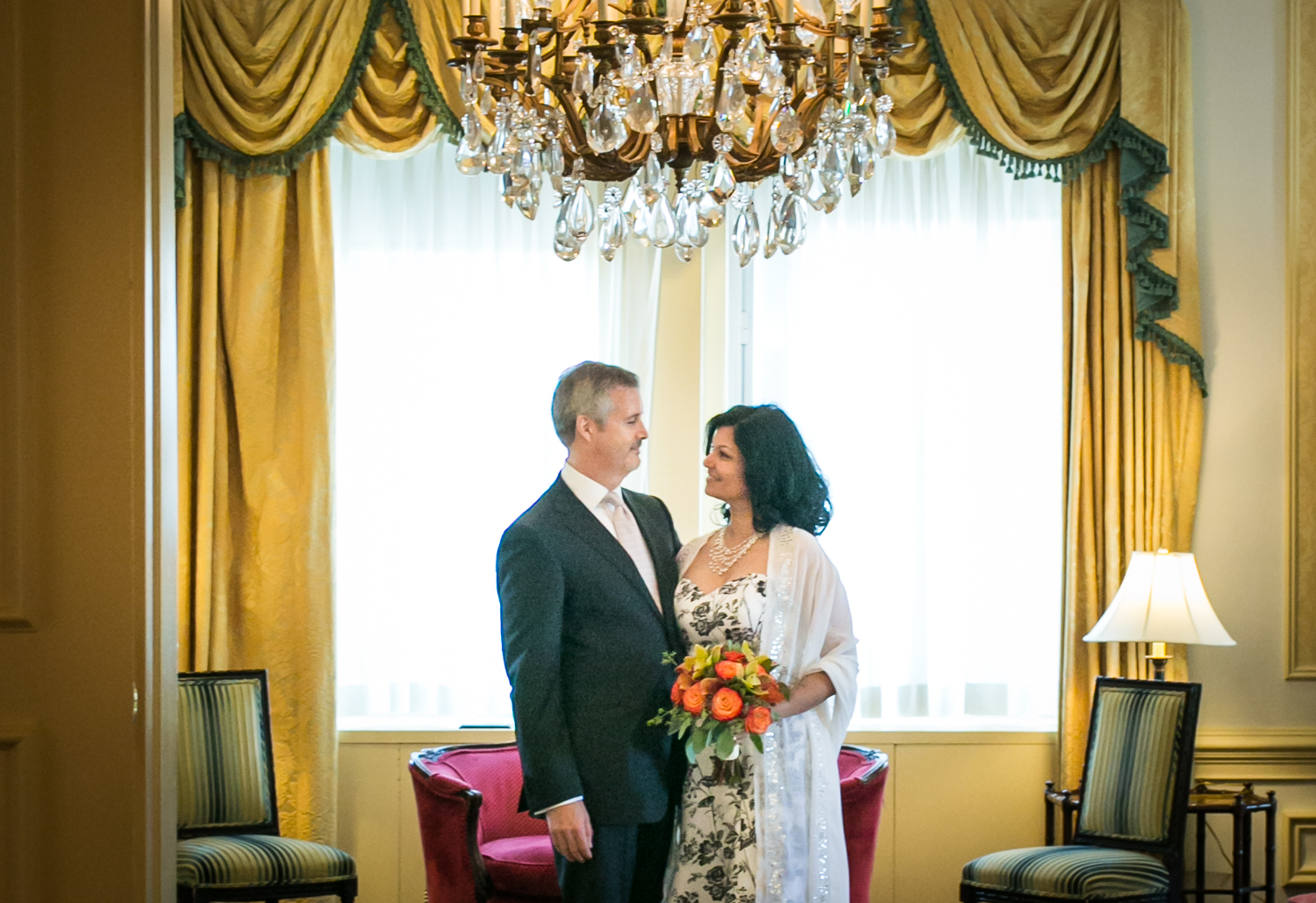 Couple looking at each other underneath chandelier at a Waldorf Astoria wedding