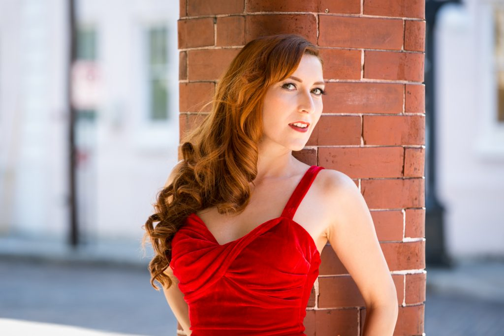 Model wearing red velvet dress against brick background at a pinup photography shoot
