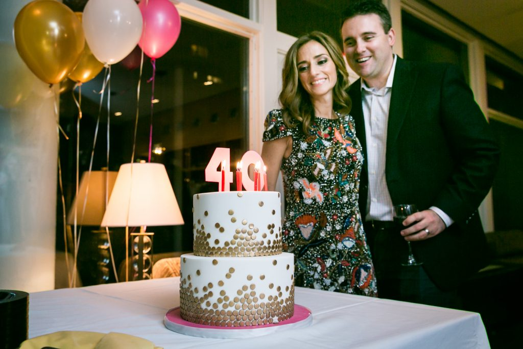 Birthday party photos of couple standing to side of cake