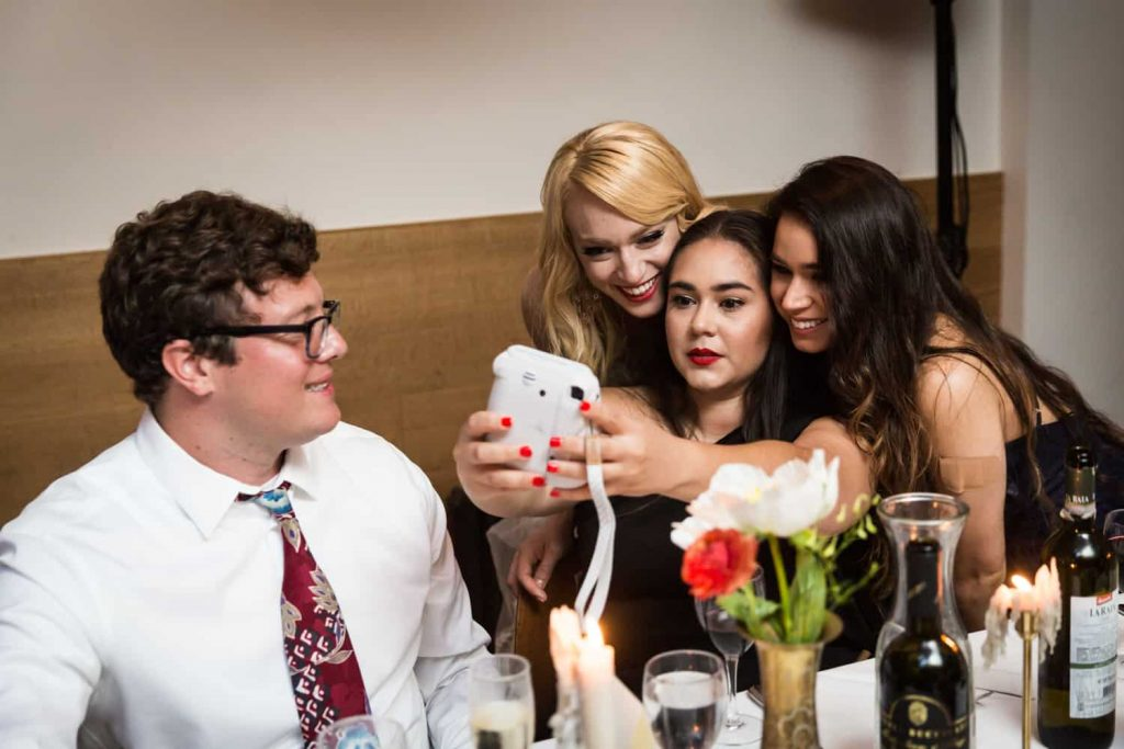 Bride taking selfie with guests at table during reception