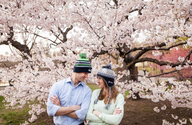 Couple wearing knit caps in front of cherry blossom trees