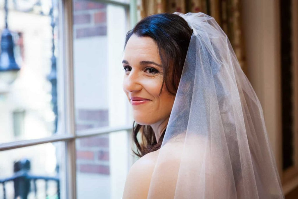 Bride looking over shoulder by a window for an article on the mysteries of photo editing