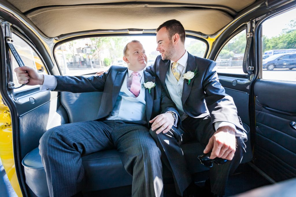 Two men in the back of a taxi cab at an Brooklyn Botanic Garden wedding
