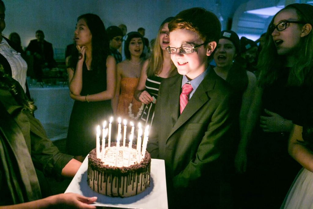 Boy blowing out birthday candles at a birthday party