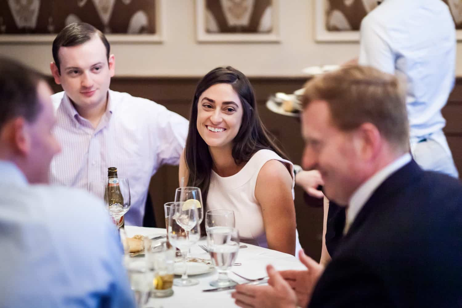Couple at table listening to other guests at a Hoboken rehearsal dinner