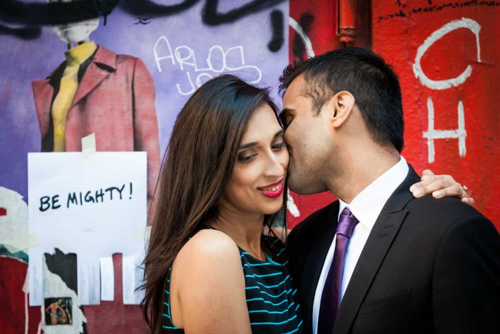 Man kissing woman on side of head with graffiti in background for an article entitled,' How I get clients comfortable in front of the camera'