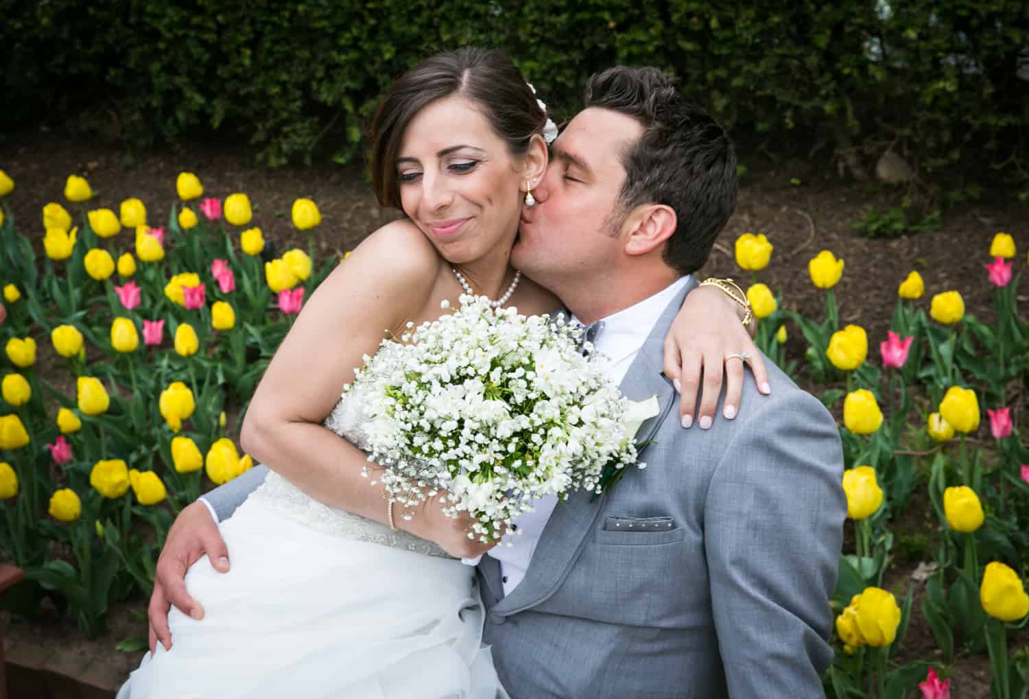 Groom kissing bride on cheek for an article called 'Do you need a second photographer?'