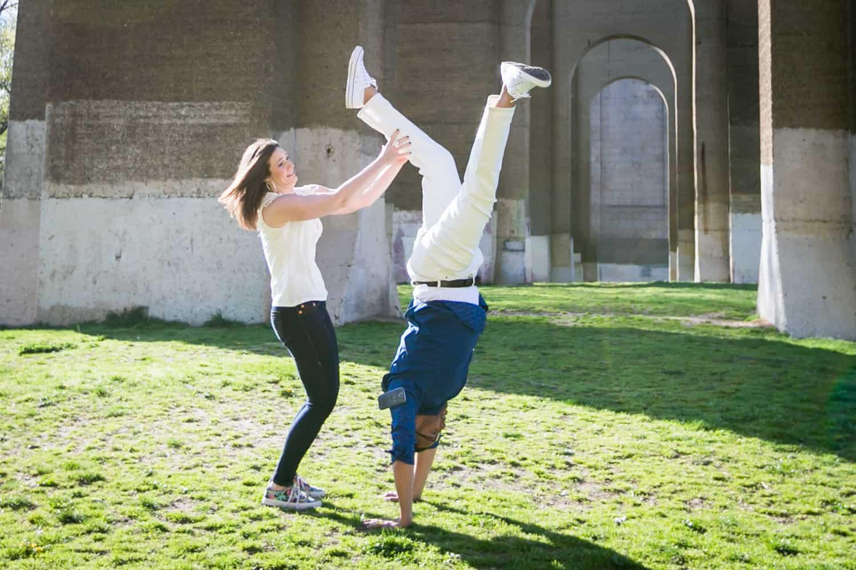 Woman holding man's legs during an Astoria Park engagement shoot