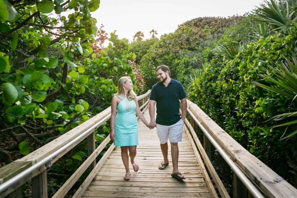Couple holding hands and walking on boardwalk during a Coral Cove Park engagement shoot