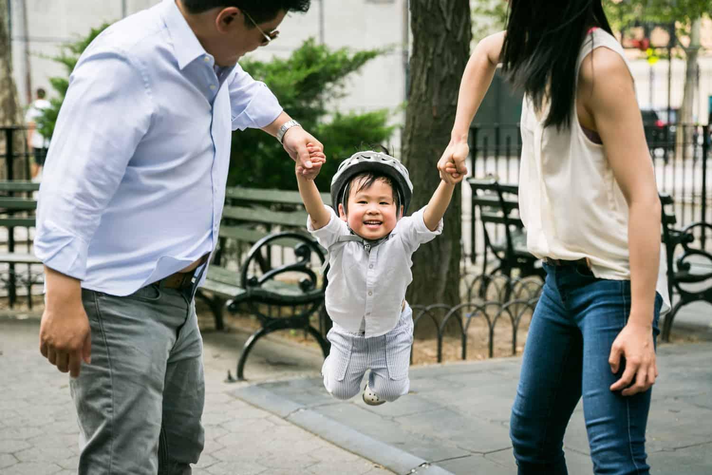 Chelsea family portrait of parents swinging little boy wearing bike helmet