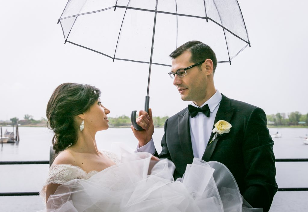 Groom holding clear umbrella over bride for an article on NYC rainy day photo tips