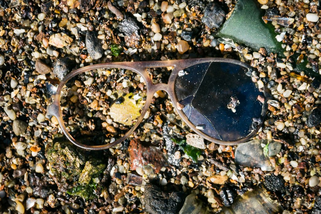 Dead Horse Bay photos of colorful trash and sunglasses on beach