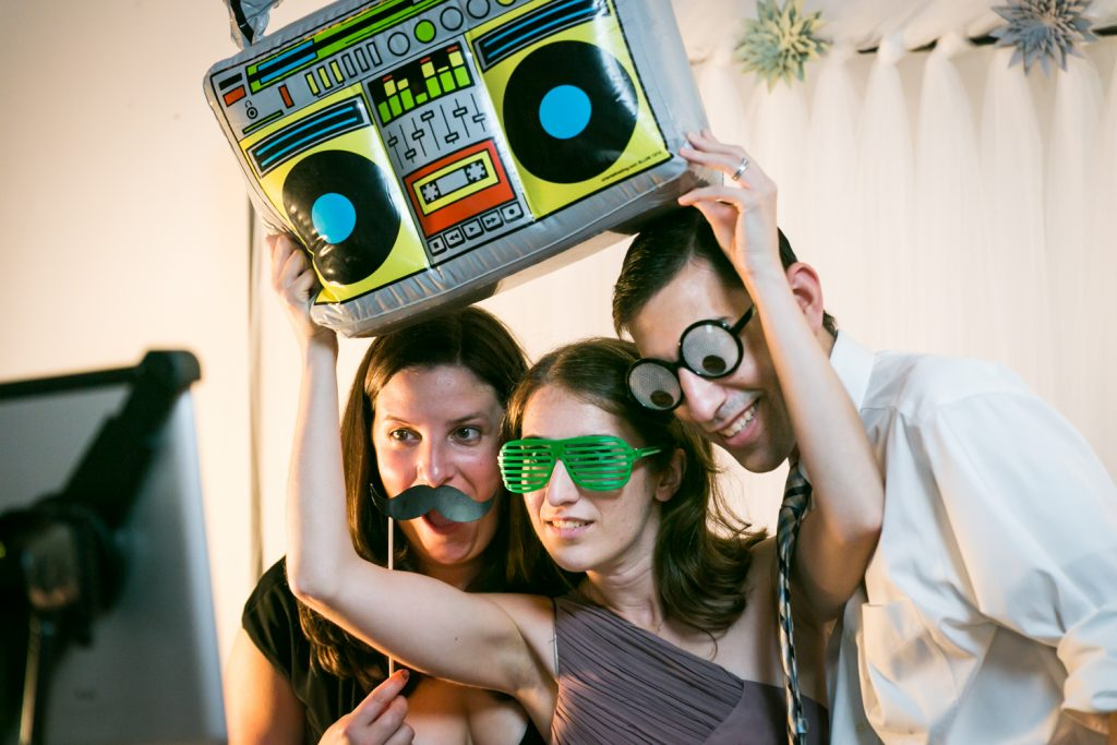 Three guests playing with props in a photo booth for an article on event entertainment ideas