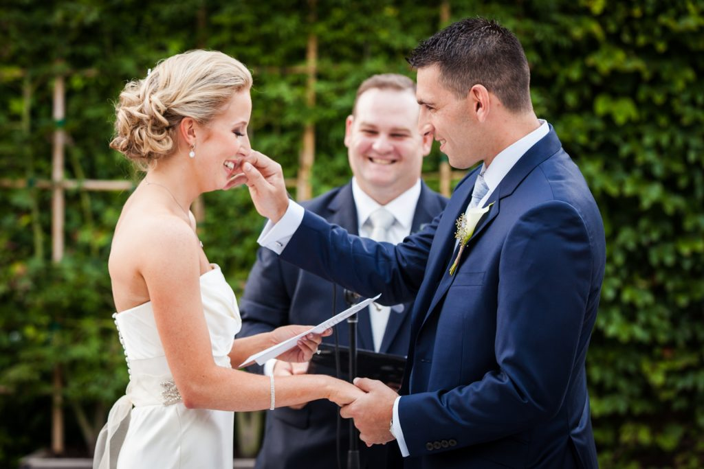 Groom wiping tear from bride's face during ceremony for an article on how to become a wedding officiant in NYC