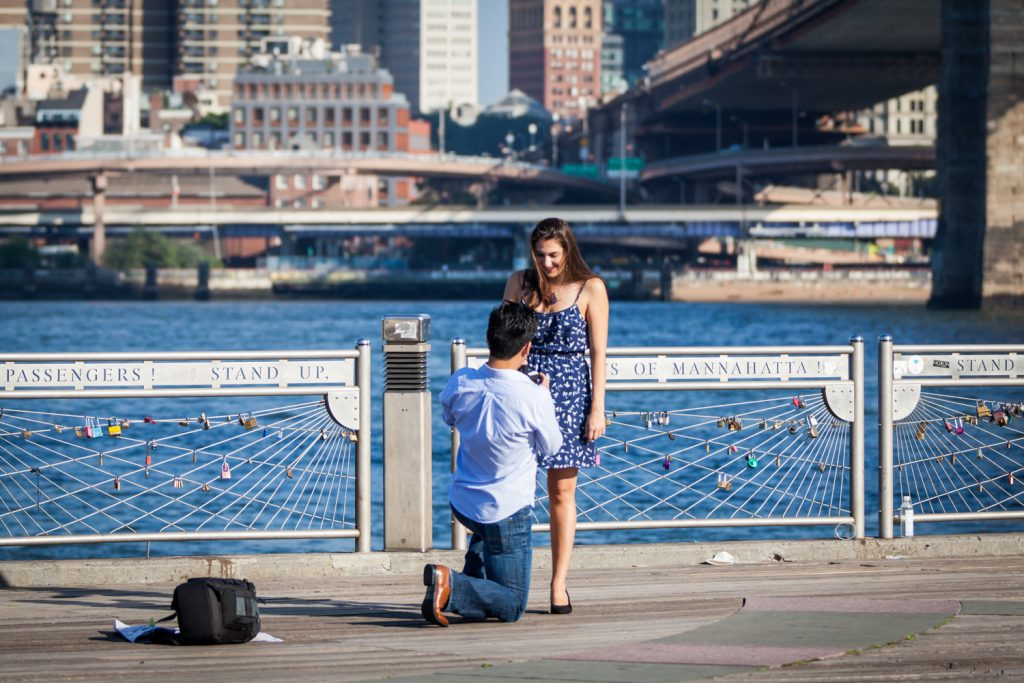 Man asking girlfriend to marry him on bended knee for article on how to plan a surprise marriage proposal