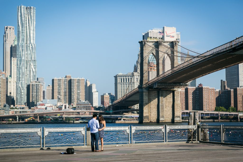 Man asking girlfriend to marry him against Brooklyn Bridge