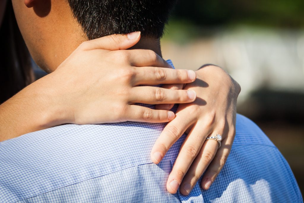 Close up of woman's hands wearing engagement ring for article on how to plan a surprise marriage proposal
