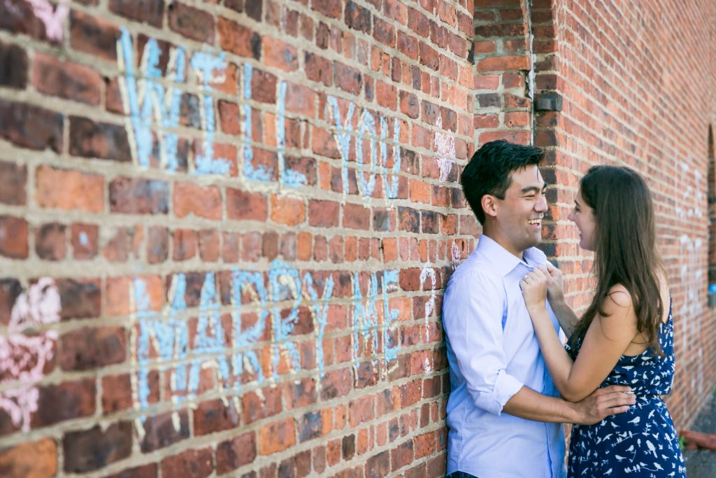 Couple leaning against brick wall with 'Will you marry me?' sign on it